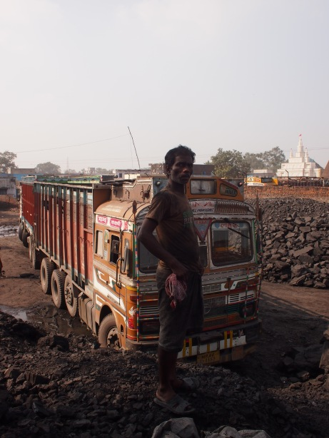 preparing to move coal from one truck to another.