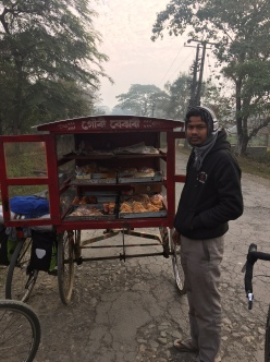 Cycling beyond Sibasagar, Assam. We met this Bihar migrant working in a bakery at the town. He was off to hawk the day's production from his baker's cycle cart.