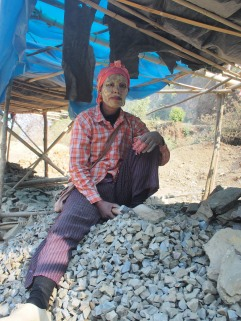 A woman, her face protected from the sun, breaks stone for the Kaladan Highway. Lawangtlai, Mizoram